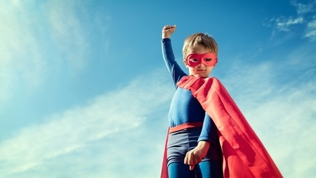 Young boy wearing superhero costume