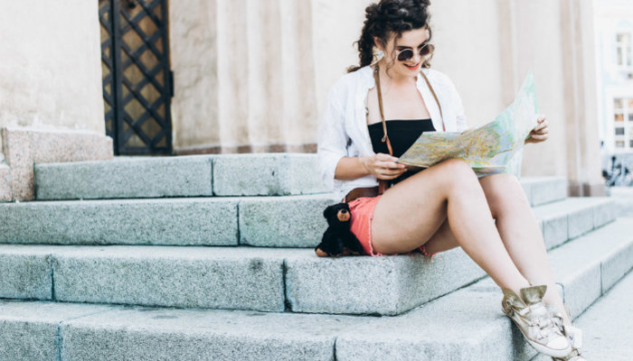 Young woman sitting on stairs reading map