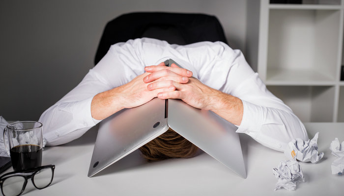 Businessman hiding under laptop