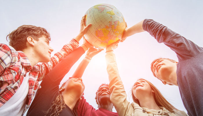 Group of multiracial teenagers holding globe