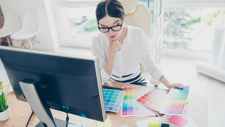 Graphic designer at work looking at colour swatches