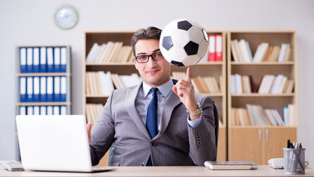 Businessman spinning football on finger