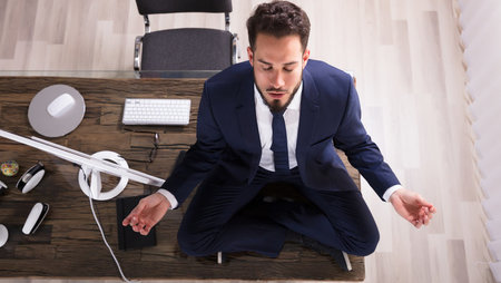 Young businessman sitting on his desk and doing yoga in the office