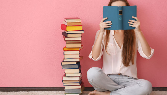 Young woman sitting on the floor next to a pile of books and reading a book