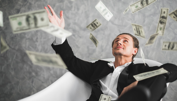Rich businessman sitting on an armchair and throwing money into the air