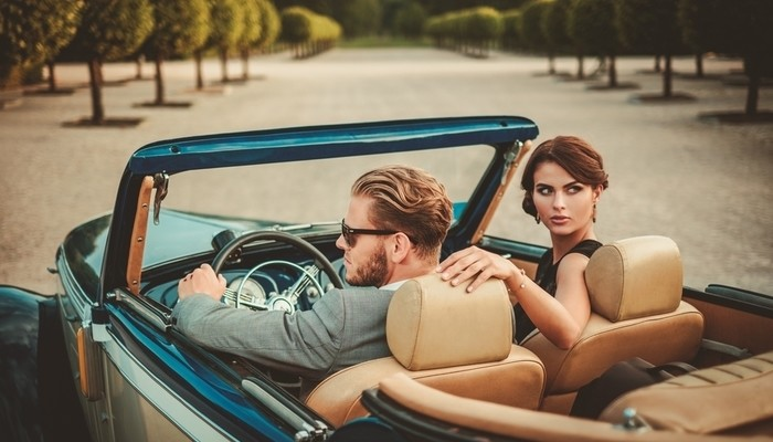 Wealthy young couple in a classic convertible car
