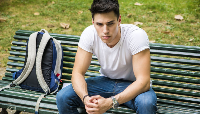 Sad young man sitting on a bench in a park