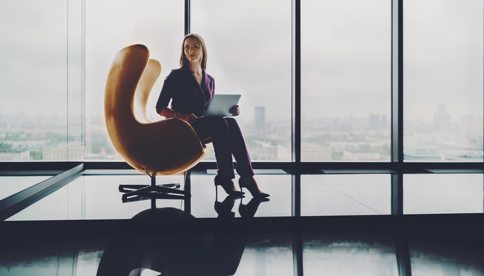 Young business woman sitting in a curved armchair in a skyscraper office