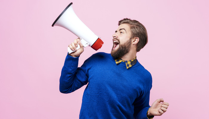 Cheerful young man shouting into a megaphone against a pink background