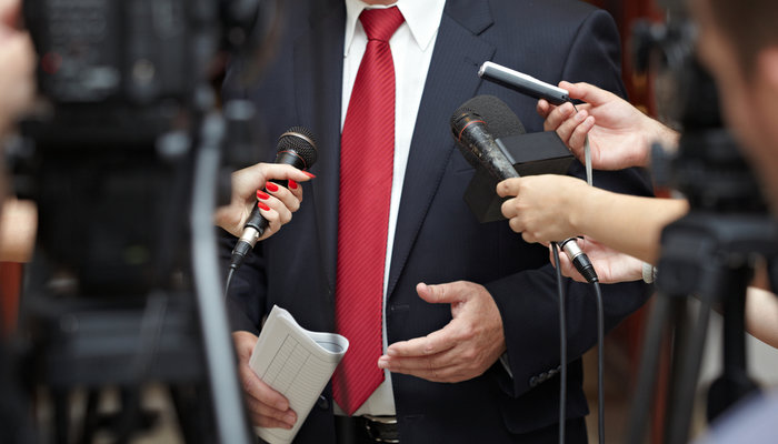 Close-up of a businessman being interviewed by a group of reporters