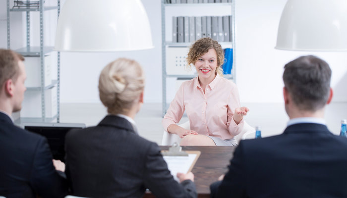 A smiling woman with a panel of interviewers during a job interview