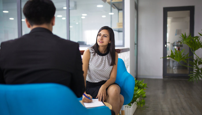 Young woman taking notes while chatting with a man in an office