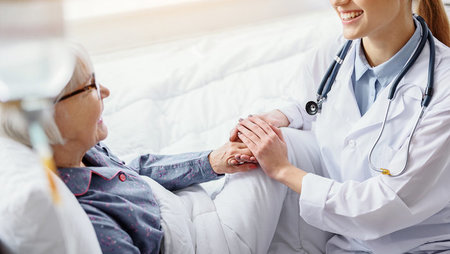 A smiling female doctor holding an elderly patient's hand