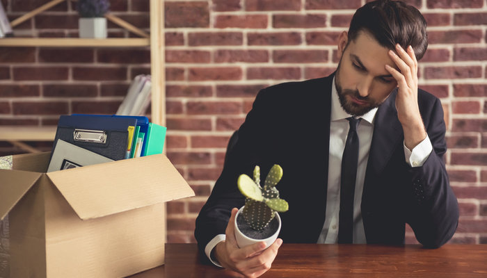 A young, sad businessman holding a cactus and packing his belongings in a cardboard box