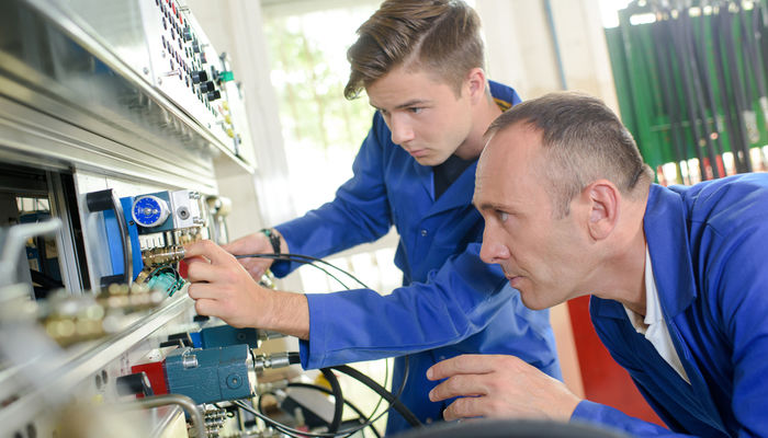 A mechanical engineer training a young apprentice