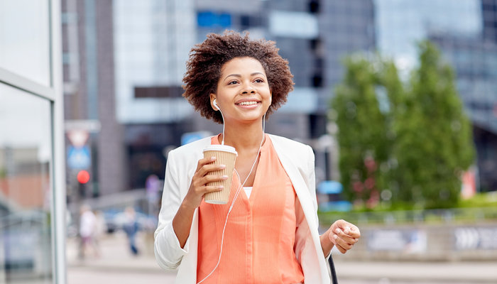 A young African American woman wearing headphones and drinking coffee while walking down a street