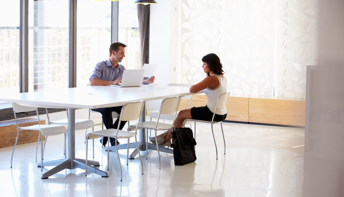 A businessman interviewing a female applicant in a spacious meeting room