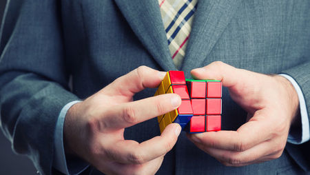 A close-up of a businessman solving a Rubik's cube