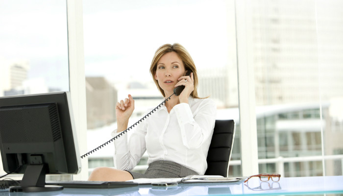 A businesswoman speaking on the phone in a brightly lit office