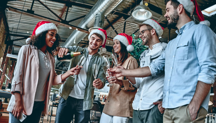 A group of people wearing Santa hats, drinking champagne and celebrating Christmas